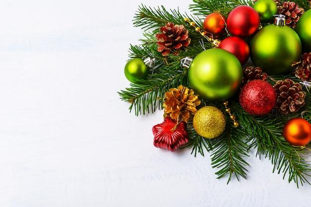 Grüne weihnachtsverzierungen, tannenzweige, roter stern und flitter