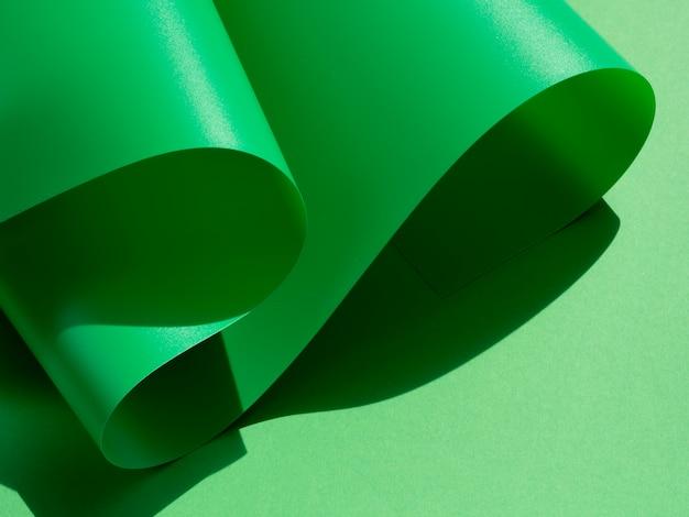 Grüne wellen von gebogenen blättern papier