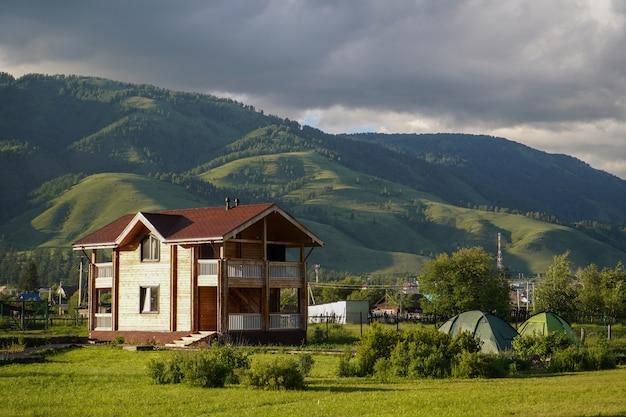 Grüne wiese mit touristischen häuschen und touristischen zelten und gewachsenen bergen