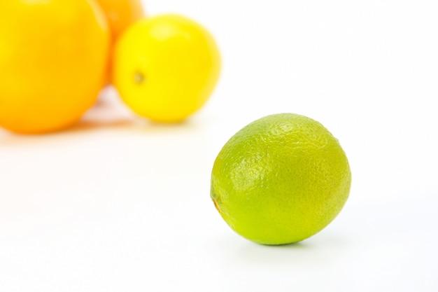 Grüne zitrone auf dem hintergrund verschiedener zitrusfrüchte auf weißem hintergrund