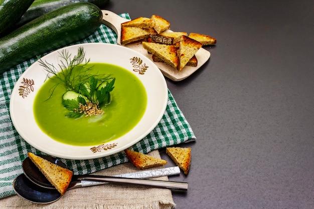Grüne zucchini-cremesuppe. gesundes veganes (vegetarisches) essen, knuspriger toast, sesam, ganze reife früchte, frisches grün. steinbetonhintergrund, kopienraum