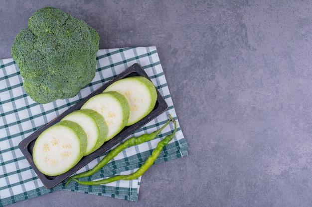Grüne zucchini und brokkoli isoliert auf blauer oberfläche