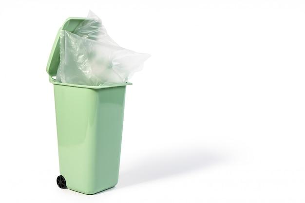 Grüner abfall, müll, behälter für nassen abfall oder recyclingbehälter mit transparenter plastiktüte darauf lokalisiert auf weißem hintergrund. grüne gabage-kunststoffbehälter für das umwelt- und recyclingkonzept.
