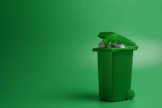 Grüner abfalleimer auf einem grünen hintergrund. ökologisches konzept.