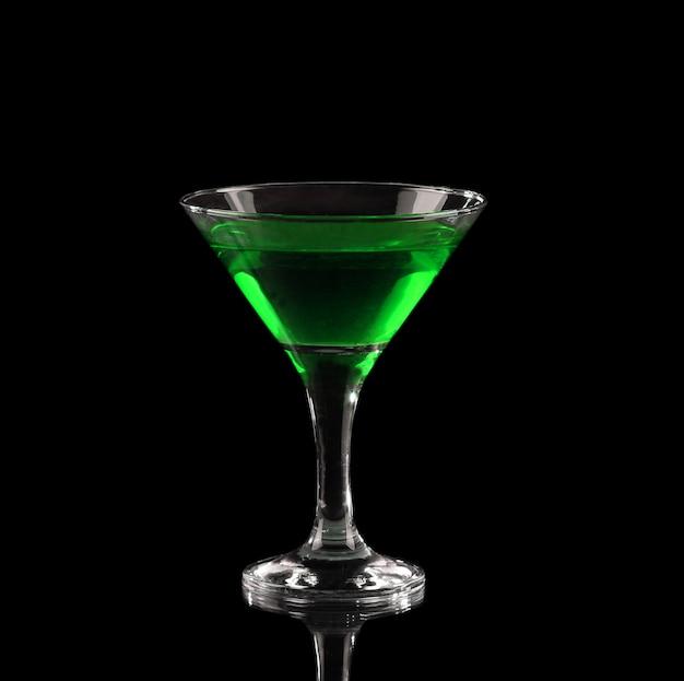 Grüner alkoholischer cocktail in einem glas auf schwarz