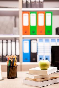 Grüner apfel auf bücherstapel neben einem notizbuch und bleistiften auf dem tisch mit einem verschwommenen weißen brett im rücken. schulkonzept