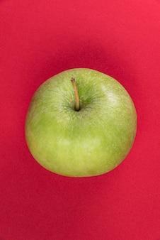 Grüner apfel auf rotem grund
