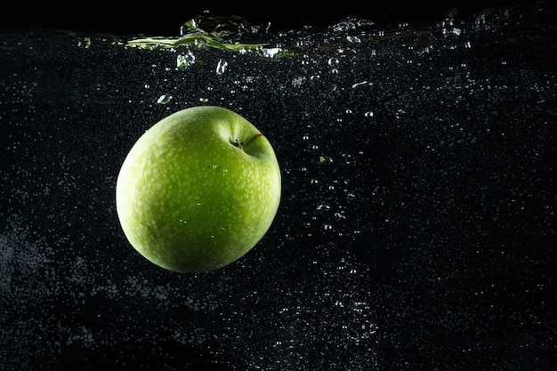 Grüner apfel, der auf schwarzem hintergrund ins wasser spritzt.