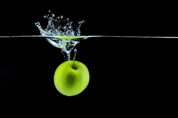 Grüner apfel, der im wasser mit einem spritzer gegen dunkle nahaufnahme fällt