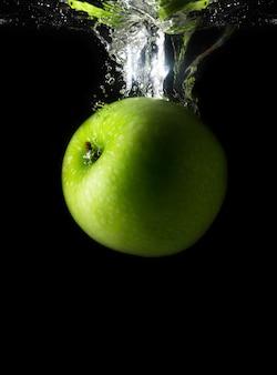 Grüner apfel, der in wasser fällt