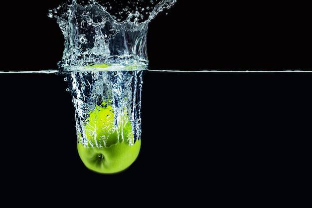 Grüner apfel, der in wasser mit einem spritzer gegen dunklen hintergrund nah oben fällt