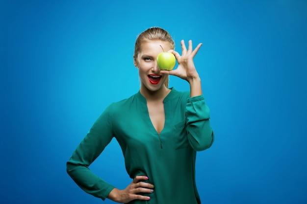 Grüner apfel des schönen jungen lächelngriffs der eignungsfrau glücklichen. gesundes lebensstilfoto lokalisiert auf blauer wand