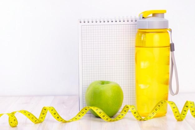 Grüner apfel, ein maßband, eine wasserflasche und ein notizbuch zum schreiben auf einem hellen hölzernen hintergrund. vorbereitung auf die sommersaison und den strand, gewichtsverlust und sportkonzept