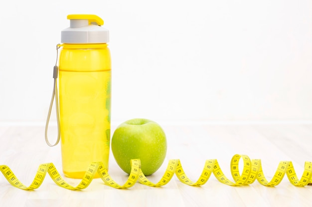 Grüner apfel, ein maßband und eine wasserflasche zum schreiben auf einem hellen hölzernen hintergrund, vorbereitung für die sommersaison und den strand, gewichtsverlust und sportkonzept