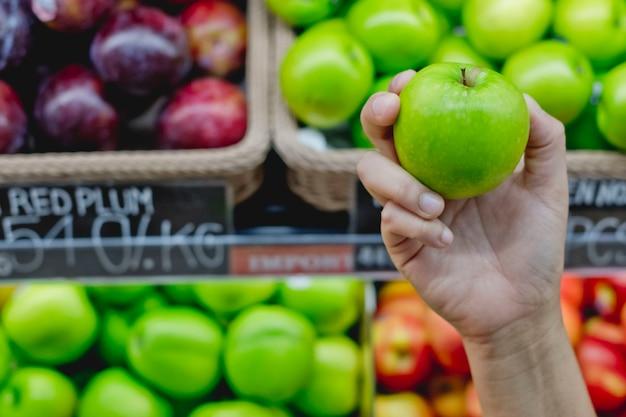 Grüner apfel in der hand mit fruchthintergrund