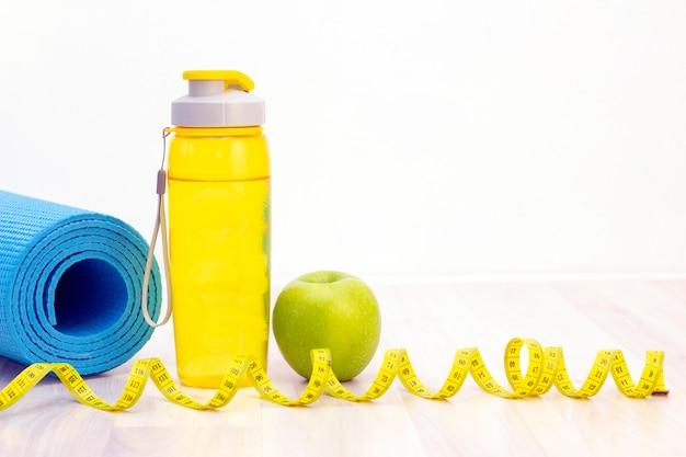 Grüner apfel, maßband, wasserflasche und sportmatten auf einem hellen hölzernen hintergrund. gewichtsverlust und sportkonzept