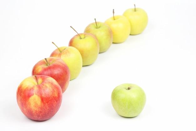 Grüner apfel neben anderen äpfeln auf weißem hintergrund