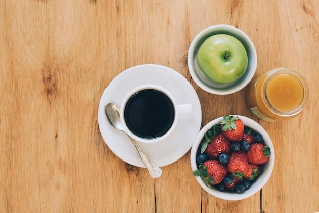 Grüner apfel; süße marmelade; beeren und schwarze kaffeetasse auf hölzernem strukturiertem hintergrund