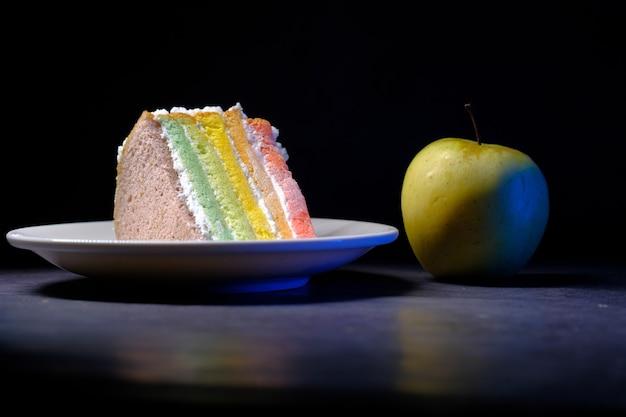 Grüner apfel und ein bäckerkuchen auf schwarzem hintergrund