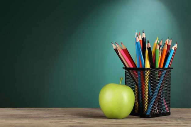 Grüner apfel und metallbecher mit buntstiften auf schreibtisch auf grünem tafelhintergrund