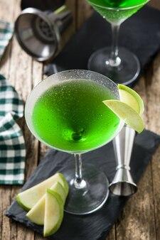 Grüner appletini-cocktail auf holztisch