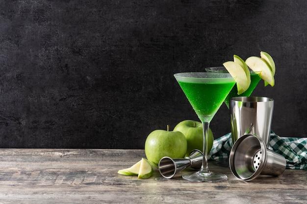 Grüner appletini-cocktail im glas auf holztisch
