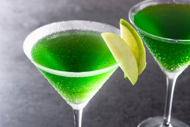 Grüner appletini-cocktail im glas auf schwarz