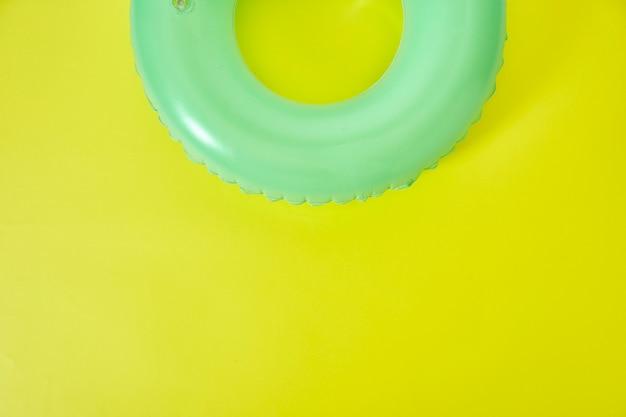 Grüner aufblasbarer ring auf gelbem hintergrund