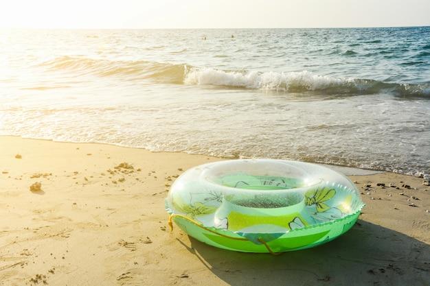 Grüner aufblasbarer runder rohr- oder plastikschwimmring auf dem sandstrand mit sonnenlicht am abend