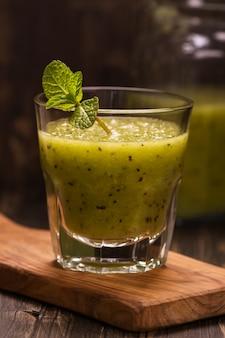 Grüner auffrischungssmoothie mit kiwi, gurke und apfel. getöntes bild