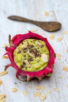 Grüner avocado-smoothie in drachenfruchthaut mit mandelflocken und chiasamen zum frühstück, nahaufnahme. das konzept der gesunden ernährung, superfood. bali, indonesien