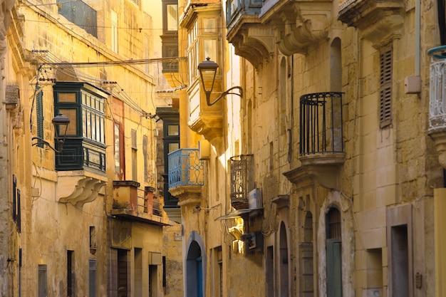 Grüner balkon, traditionelle häuser, die fassade mit sandsteinen und bedeckten balkonen in malta errichten
