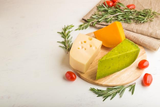 Grüner basilikumkäse und verschiedene käsesorten mit rosmarin und tomaten