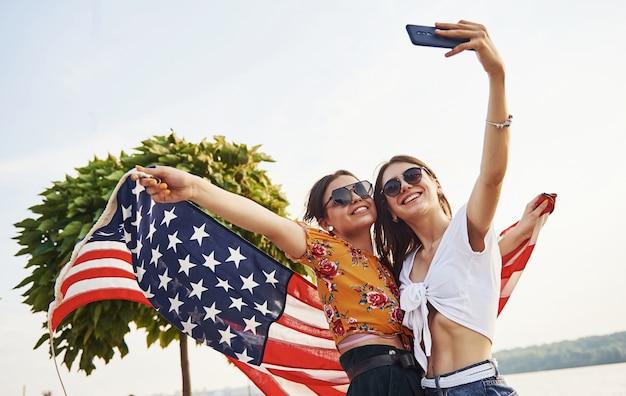 Grüner baum im hintergrund. zwei patriotische fröhliche frauen mit usa-flagge in den händen machen selfie im freien im park.