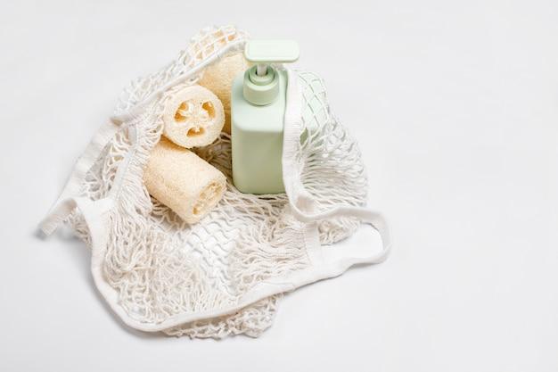 Grüner behälter für shampoo, conditioner oder flüssigseife im öko-beutel. luffa- oder luffa-waschlappen, gemüseschwamm, alternative zu kunststoff, null abfall, umweltfreundlich.