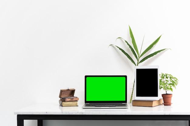 Grüner bildschirm des schwarzen bildschirms des laptops und der tablette auf marmorschreibtisch