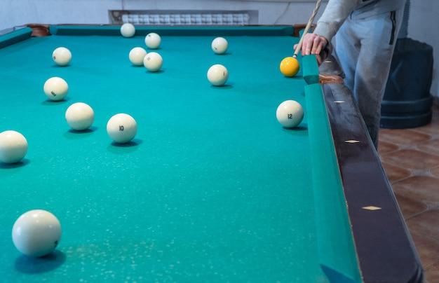 Grüner billardtisch mit weißen kugeln. junger mann spielt billard