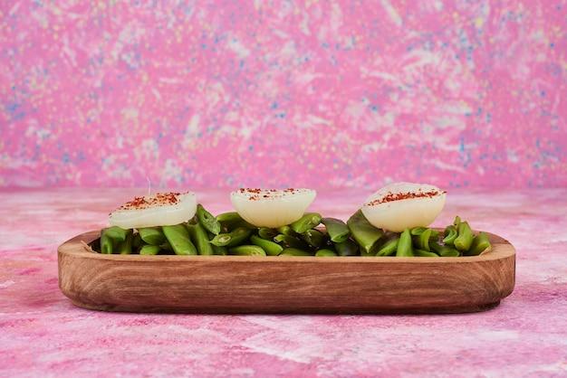 Grüner bohnensalat und snacks auf holzplatte.