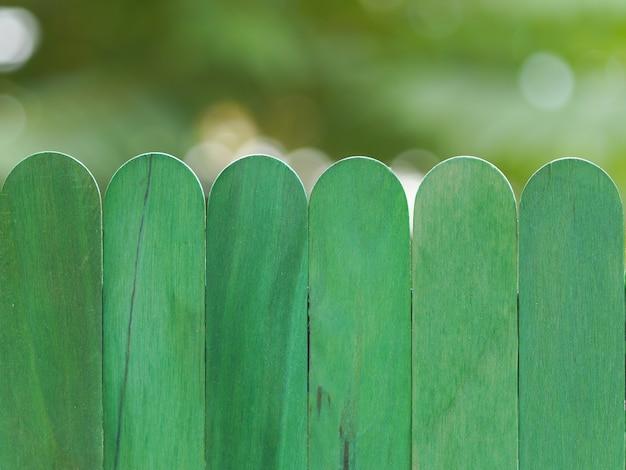 Grüner bretterzaun gegen bokeh hintergrund