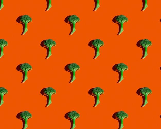 Grüner brokkoli auf orangem hintergrundmuster