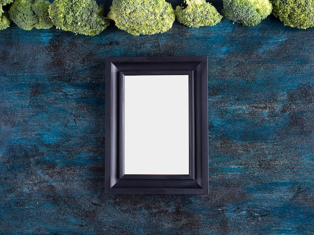 Grüner brokkoli mit leerem rahmen auf tabelle