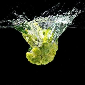 Grüner brokkoli spritzt in sauberes wasser über dem schwarzen hintergrund