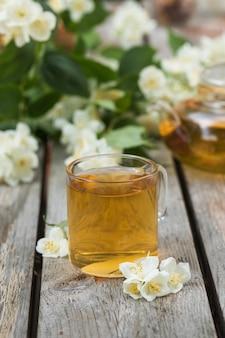 Grüner chinesischer tee mit jasmin in einer tasse mit jasminblüten