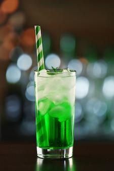 Grüner cocktail auf dem tisch im dunkeln
