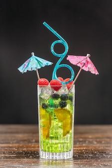 Grüner cocktail in einem hohen glas, dekoriert mit orange, himbeeren und blaubeeren