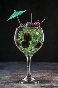 Grüner cocktail mit eis und kirschen in einem glas, das mit regenschirm verziert wird