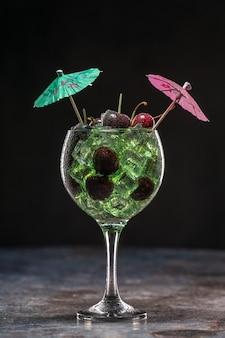 Grüner cocktail mit eis und kirschen in einem glas, das mit regenschirmen verziert ist Premium Fotos