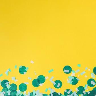 Grüner confetti auf gelbem hintergrund mit exemplarplatz