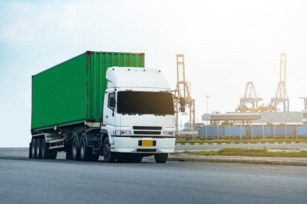Grüner container-lkw der fracht in schiffshafen logistik