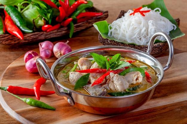 Grüner curry mit huhn auf hölzernem hintergrund, thailändische küche